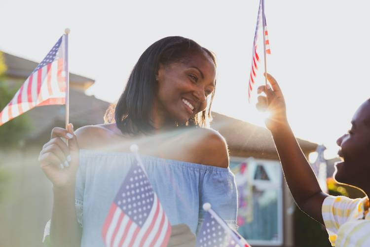 young Black mother and son celebrating the 4th of july with American flags waving in the air