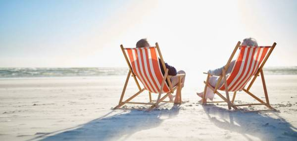 two people relaxing on a beach in orange and white stripped beach chairs