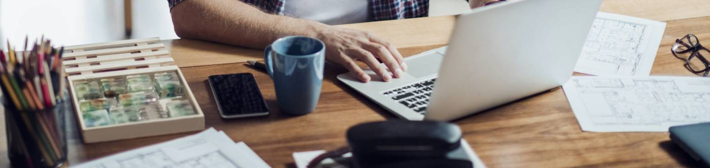 man working remotely with laptop and documents